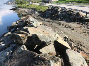 Steinmassar plassert på begge sider av veg ned mot sjøen