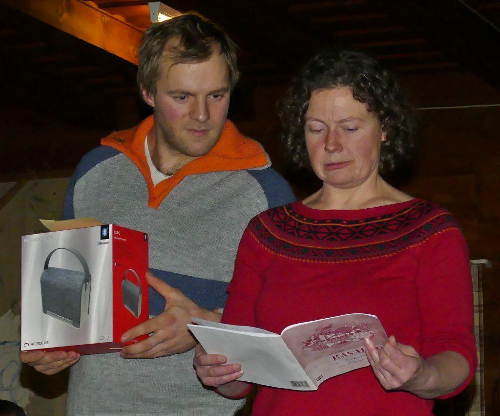 Jorunn Børve inn ut kven som har vunne på bok. Jan Sandven står klar med gevinsten.